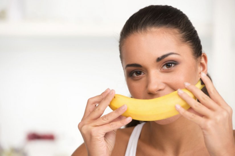 Банан с кожурой и молодая девушка